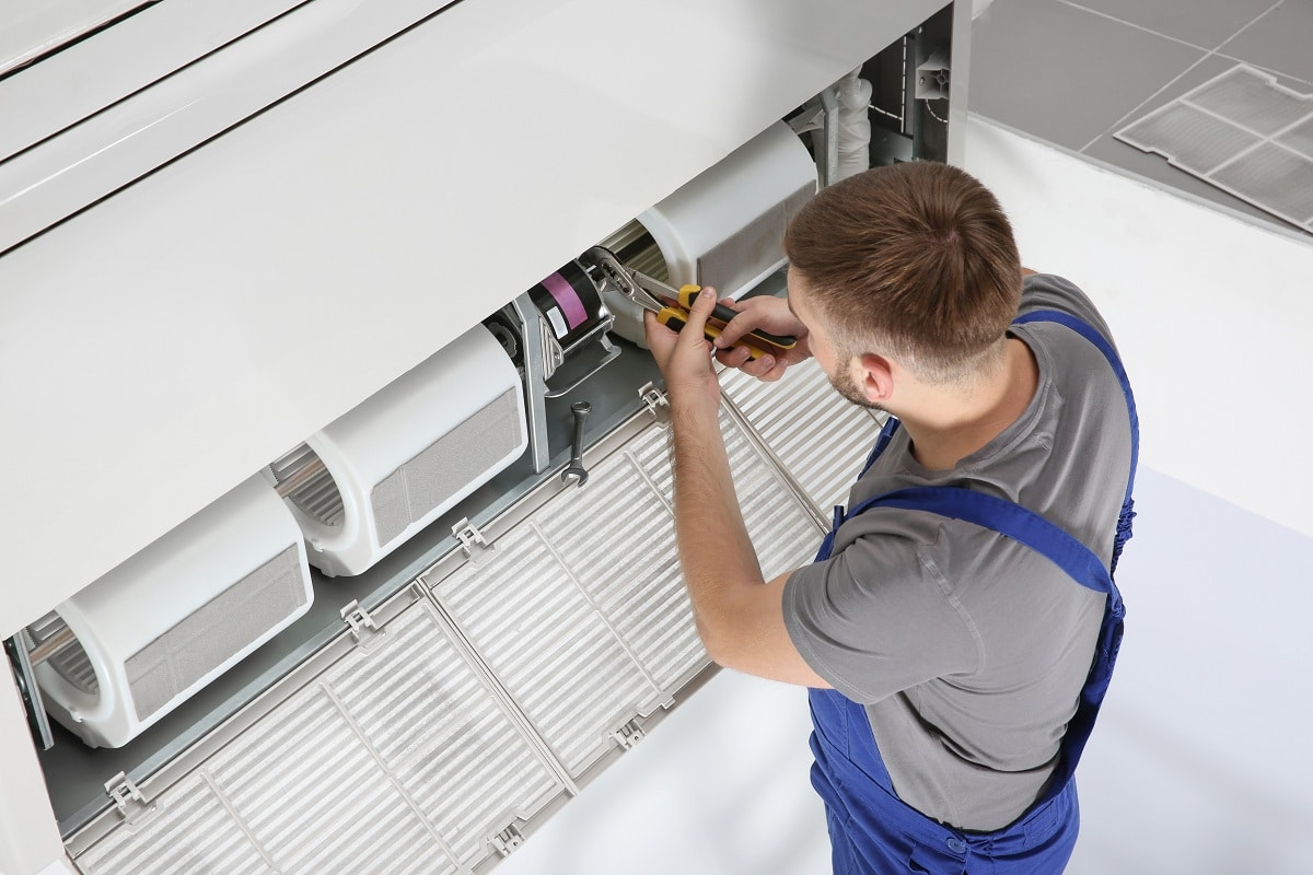 ac technician repairing unit